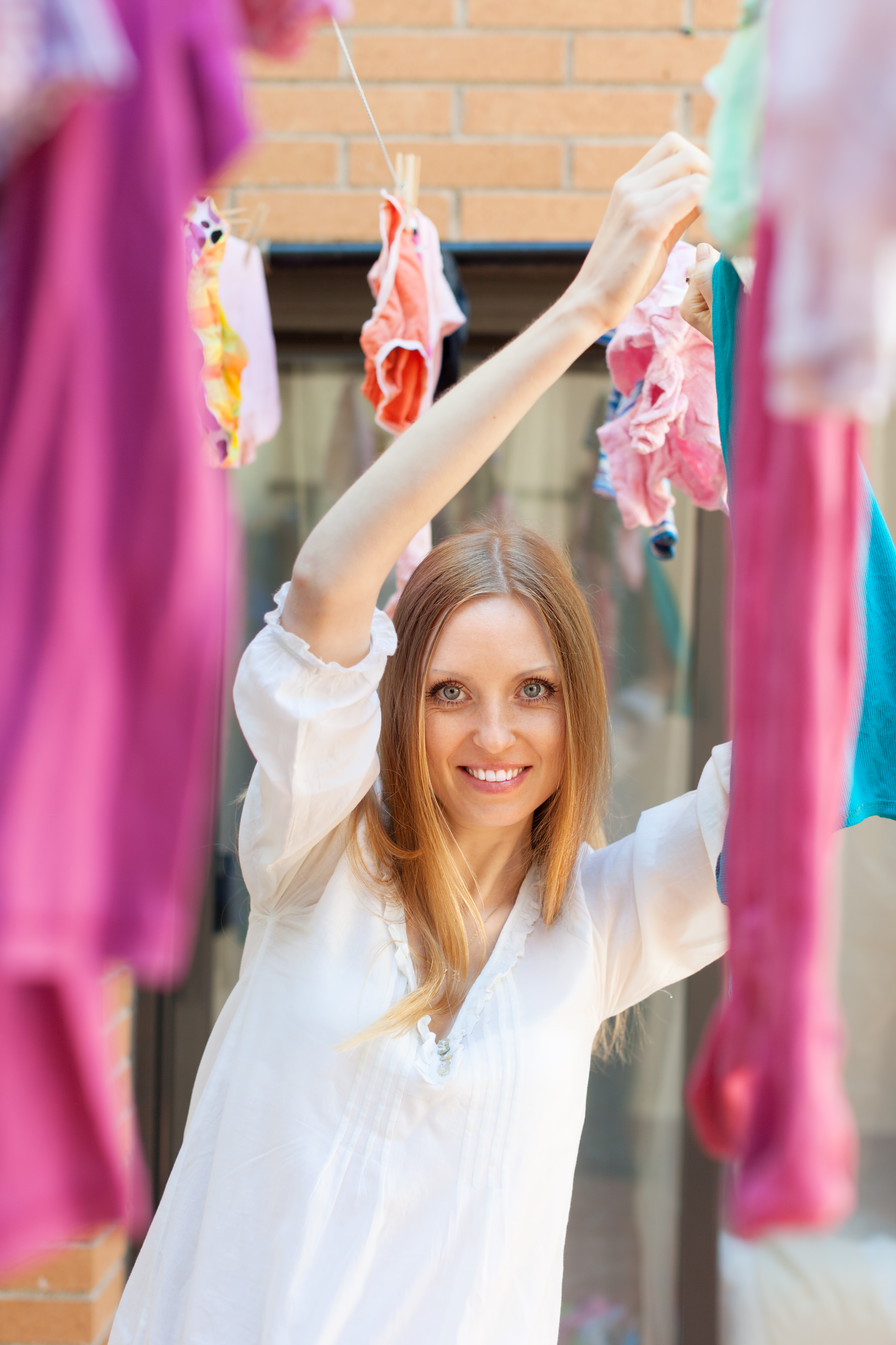 woman hanging clothes to dry  after laundry